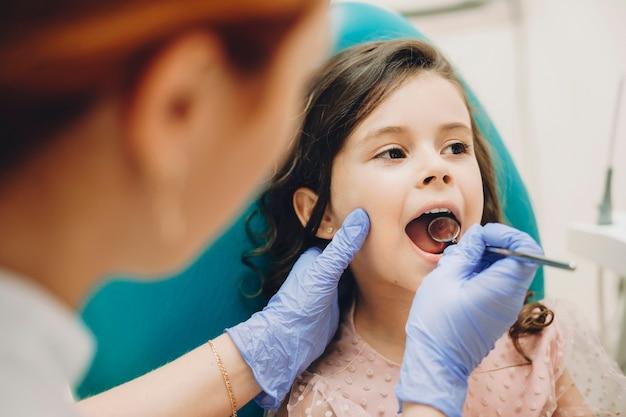 Close up van een schattig klein meisje doet een tiende onderzoek in een pediatrische stomatologie.