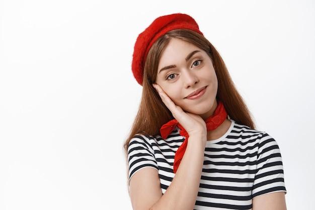 Close-up van een schattig lachend meisje in een baret die naar voren kijkt, mooi, starend met een tedere gezichtsuitdrukking, staande over een witte muur