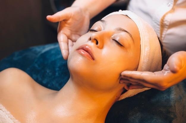 Close-up van een schattig vrouwtje leunend op een spa-bed met gesloten ogen met gezichtsmassage routine in een spa-centrum.