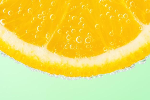 Close-up van een schijfje sinaasappel in soda water met bubbels
