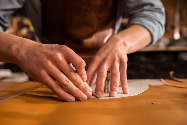 Close up van een schoenmaker snijden leer