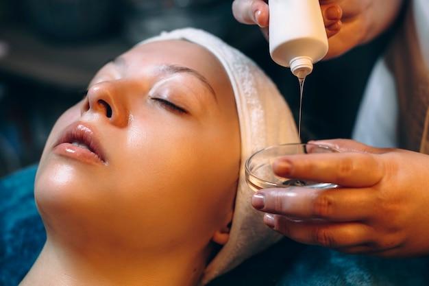Close-up van een schoonheidsspecialist overhandigt product uit een fles in een beker voor gezichtsmasker dat op een vrouwelijk gezicht zal worden aangebracht.