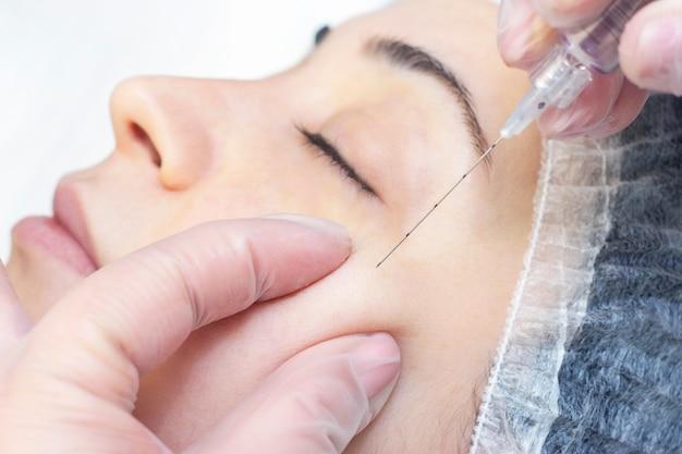 Close-up van een schoonheidsspecialiste die in de huid van het gezicht injecteert. ze houdt een spuit vast. cosmetica worden in het vrouwelijke gezicht geïntroduceerd