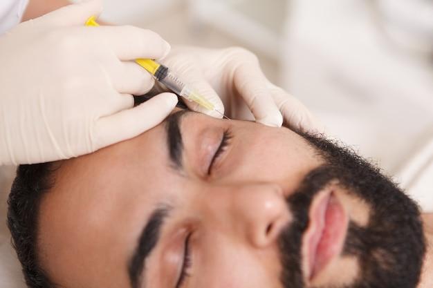 Close up van een schoonheidsspecialiste vulmiddel injecteren in gezicht van mannelijke cliënt