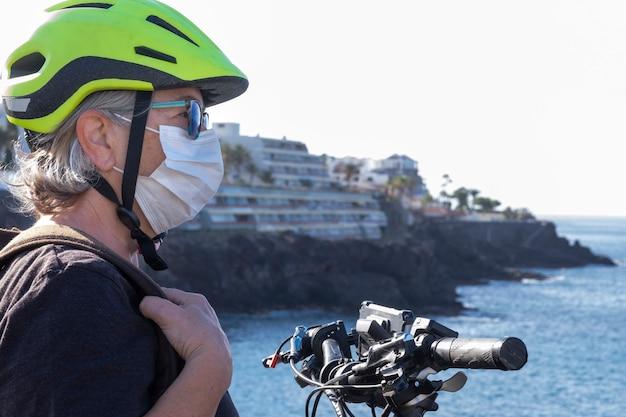 Close-up van een senior vrouw in de buitenlucht met fiets en helm genietend van de natuur en de zee