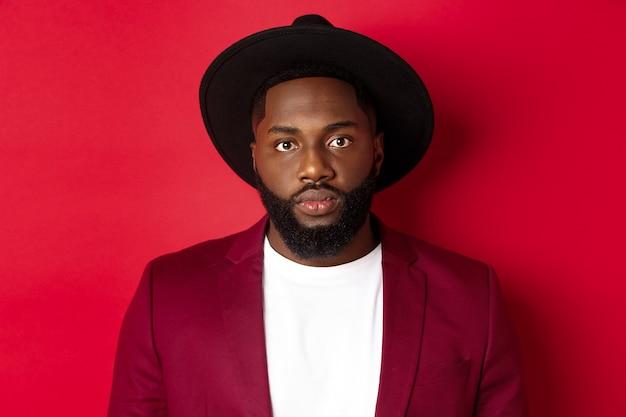 Close-up van een serieus uitziende afro-amerikaanse man in blazer en zwarte hoed, kijkend naar de camera, staande over rode achtergrond