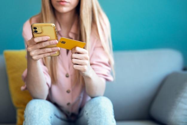 Close-up van een serieuze jonge vrouw die iets online betaalt met haar creditcard en de smartphone terwijl ze thuis op de bank zit.