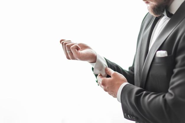 Close-up van een serieuze man die zijn manchetknopen aanpast