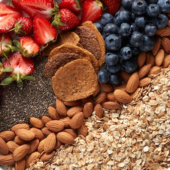 Close-up van een set ingrediënten, havermout, muesli, amandelen, snacks, bosbessen en aardbeien helften bovenaanzicht. gezond vitamine-ontbijt