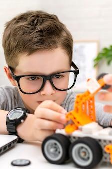 Close-up van een slimme jongen met een bril bouwt en programmeert een robotauto thuis, het kind leert ...