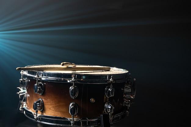Close-up van een snaredrum, percussie-instrument op een donkere achtergrond met prachtige verlichting, kopieerruimte.