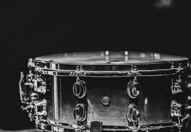 Close-up van een snaredrum, percussie-instrument op een donkere achtergrond, zwart-wit.