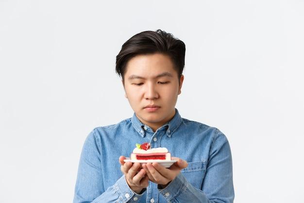 Close-up van een sombere aziatische man die verleidelijk is om stuk cake te proberen, kijkend naar het dessert met verlangen. man op dieet probeert de verleiding te weerstaan van het eten van koolhydraten, afvallen, staande witte achtergrond.
