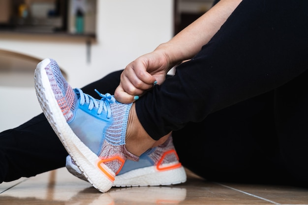 Close up van een spaanse vrouw haar lichtblauwe en oranje sneakers aantrekken Premium Foto