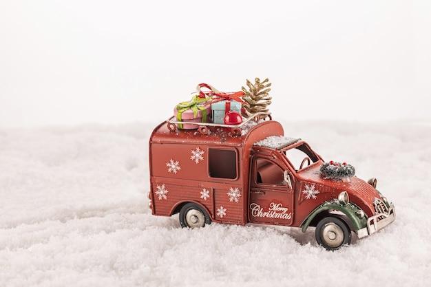 Close-up van een speelgoedauto met kerstversieringen erop op kunstmatige sneeuw tegen een witte achtergrond