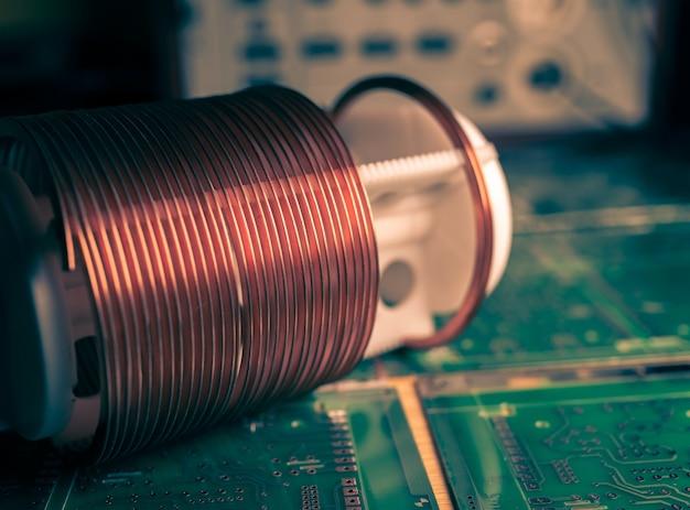 Close-up van een spoel van koperdraad die zich op een grote microschakeling bevindt