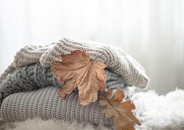 Close-up van een stapel gebreide truien met herfstbladeren op een onscherpe achtergrond.