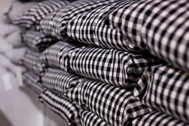 Close-up van een stapel kussens in een zwart-witte kooi. stapel kussens op een plank. de winkel verkoopt moderne grijze geruite kussens. textiles. huisdecoratie. gezellig huis. decoratieve kussens geïsoleerd