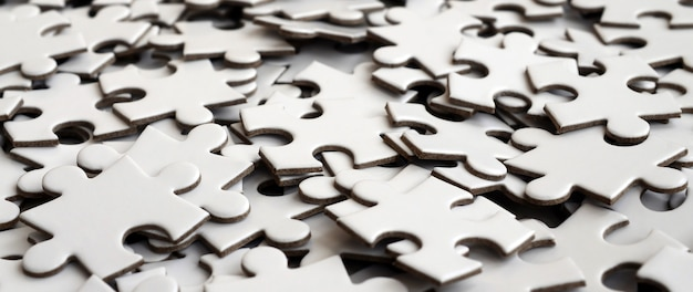 Close-up van een stapel niet-voltooide elementen van een witte puzzel