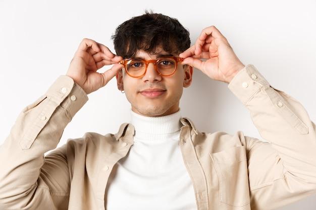Close-up van een stijlvolle hipster-man die een bril probeert in een opticienwinkel, een bril opzet en glimlacht, staande op een witte achtergrond