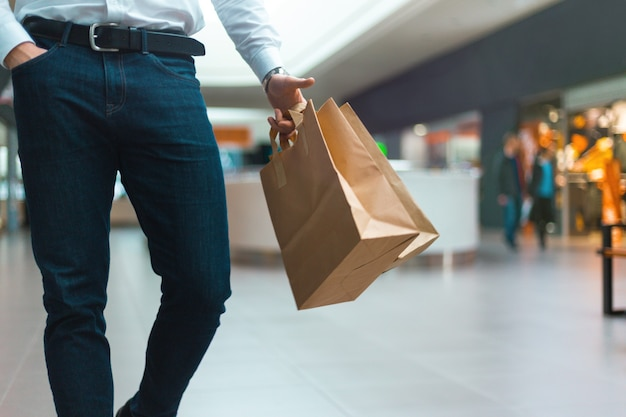 Close-up van een stijlvolle jongeman die in een winkelcentrum loopt met ecologievriendelijke boodschappentassen in de hand met goederen en kleding. verkoop, korting uitverkocht concept. seizoensgebonden uitverkocht.