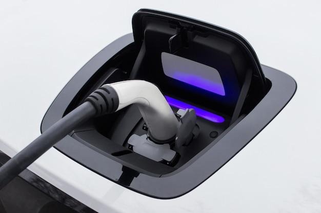 Close-up van een stopcontact voor het opladen van elektrische auto met aangesloten oplader van elektrische station
