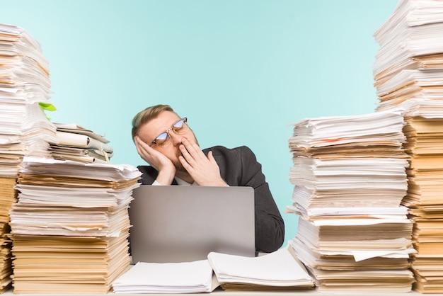 Close-up van een stressvolle zakenman moe van zijn werk op de voorgrond - afbeelding