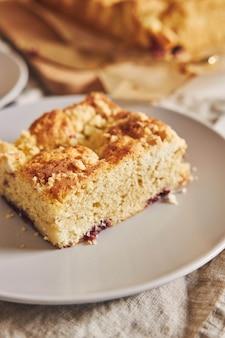 Close-up van een stuk heerlijke cake van het blad van jerry crumble op witte houten lijst