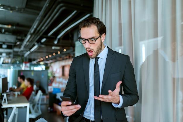 Close-up van een succesvolle zakenman gekleed in formele slijtage bericht lezen op slimme telefoon.