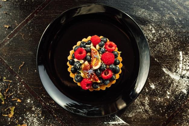 Close-up van een taart met aardbeien en bosbessen erop