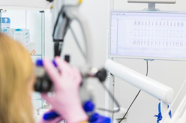 Close-up van een tandarts die door microscoop kijkt