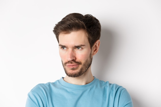Close-up van een teleurgestelde man met een baard, mokkend en naar links kijkend met een peinzend gezicht, van streek over een witte achtergrond