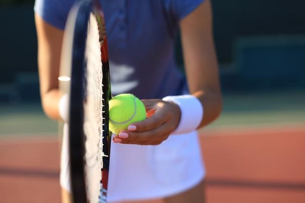 Close up van een tennisser die de bal met racket raakt.