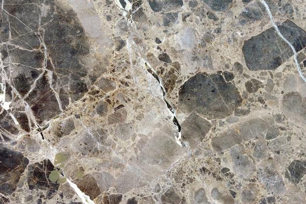 Close-up van een textuur van een grijze muur gemaakt van steen en marmer