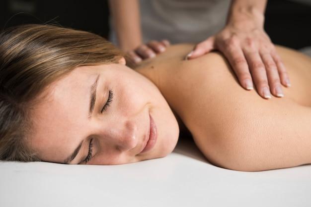 Close-up van een therapeuthand die massage geeft aan mooie jonge vrouw in kuuroord