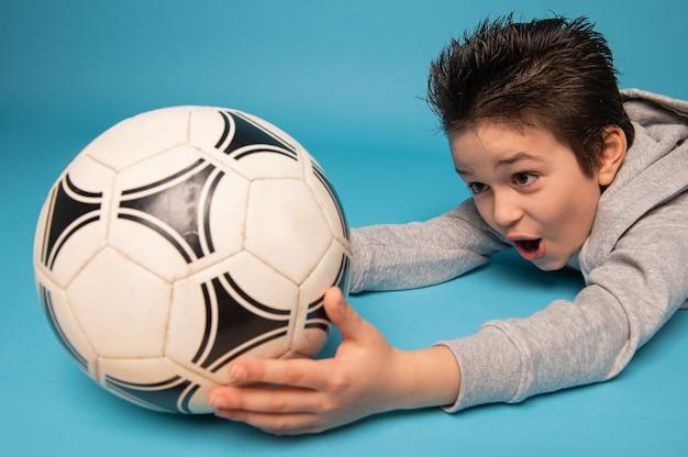 Close-up van een tiener die, keeper, een voetbalbal vangt, die op de vloer ligt