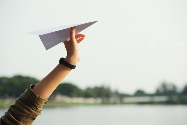 Close-up van een tienerhand die het document vliegtuig werpt