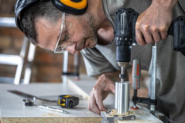 Close-up van een timmerman die met hout werkt en gereedschappen in huis bouwt