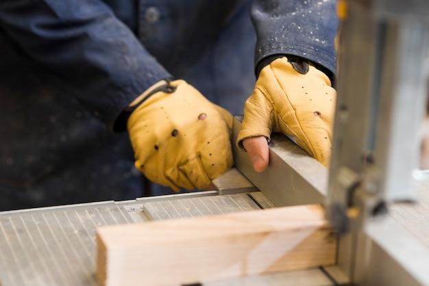 Close-up van een timmermanshanden die met houten blok aan werkbank werken