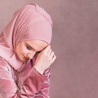 Close-up van een trieste arabische vrouw tegen studio oppervlak