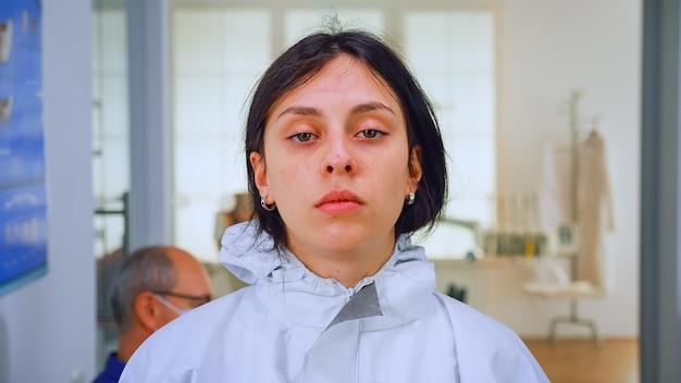 Close-up van een uitgeputte verpleegster in de tandartspraktijk die op de camera kijkt met een ppe-pak zonder gezichtsschild zittend op een stoel in de wachtkamerkliniek. concept van nieuw normaal tandartsbezoek bij uitbraak van coronavirus