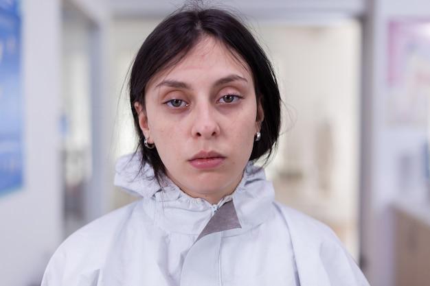 Close-up van een uitgeputte verpleegster op kantoor die op de camera kijkt en een pbm-pak draagt zonder gezichtsschild zittend op een stoel in de wachtkamerkliniek