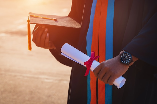 Close up van een universitair afgestudeerde met diploma en baret
