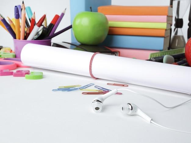 Close-up van een vel tekenpapier en schoolbenodigdheden geïsoleerd op een witte achtergrond