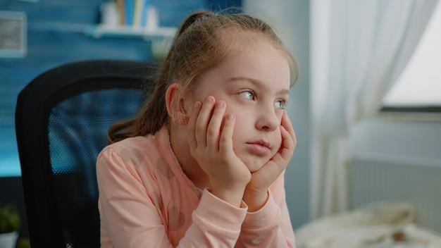 Close-up van een vermoeid kind dat naar een online les op afstand luistert