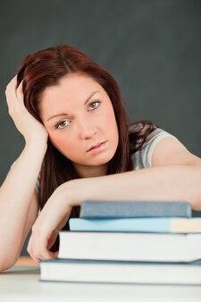 Close-up van een vermoeide student met haar onderarm om haar boeken