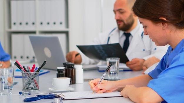 Close-up van een verpleegster die aantekeningen maakt op het klembord terwijl collega's van de radioloog op de achtergrond discussiëren over het analyseren van röntgenfoto's en het schrijven op de laptop. professionele teamworkers met medische vergadering, brainstormen