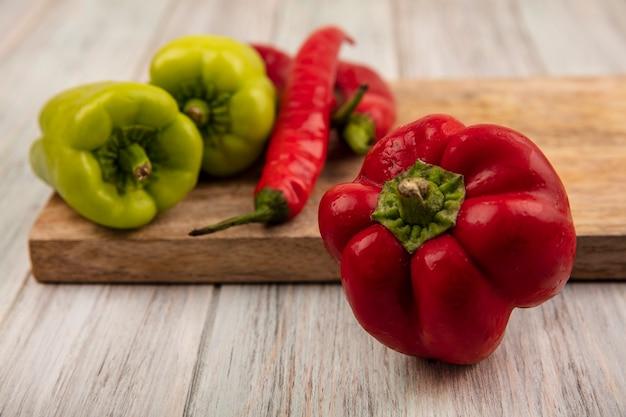 Close-up van een verse rode paprika met kleurrijke bel en chilipepers op een houten keukenbord op een grijze houten achtergrond