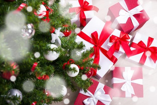 Close-up van een versierde kerstboom en een hoop cadeautjes