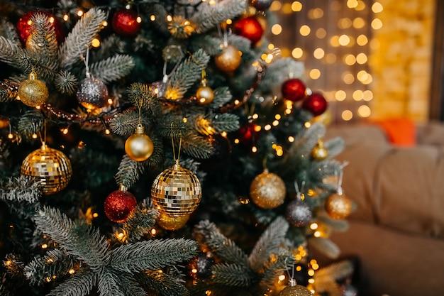 Close-up van een versierde kerstboom met rode en gouden ballen